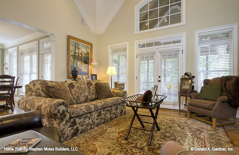 The living room offers a floral sofa, striped armchairs, and a wooden coffee table that sits on a classic area rug.