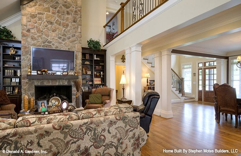 The living room includes a stone fireplace nestled between the wooden built-ins.