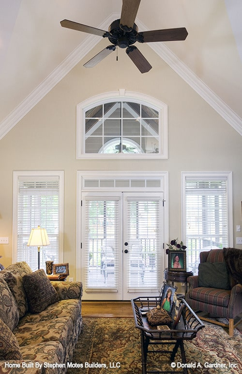 A cathedral ceiling mounted with a ceiling fan tops the living room.