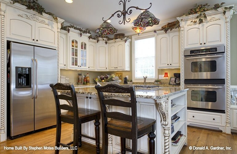 The kitchen offers white cabinetry, stainless steel appliances, granite countertops, and a breakfast island.
