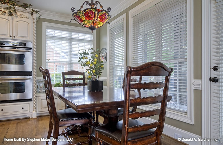 Breakfast nook with a dark wood dining set well-lit by a lovely stained glass pendant.