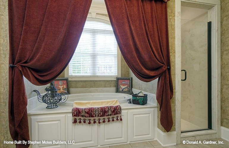 Primary bathroom with a walk-in shower and a deep soaking tub dressed in heavy red draperies.
