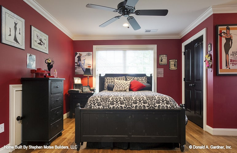 This bedroom has dark wood furnishings, hardwood flooring, and bold red walls lined with white trims.