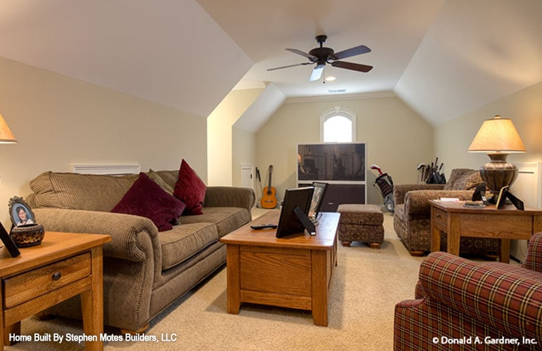 Bonus room with carpet flooring, vaulted ceiling, and fabric seats paired with wooden tables.