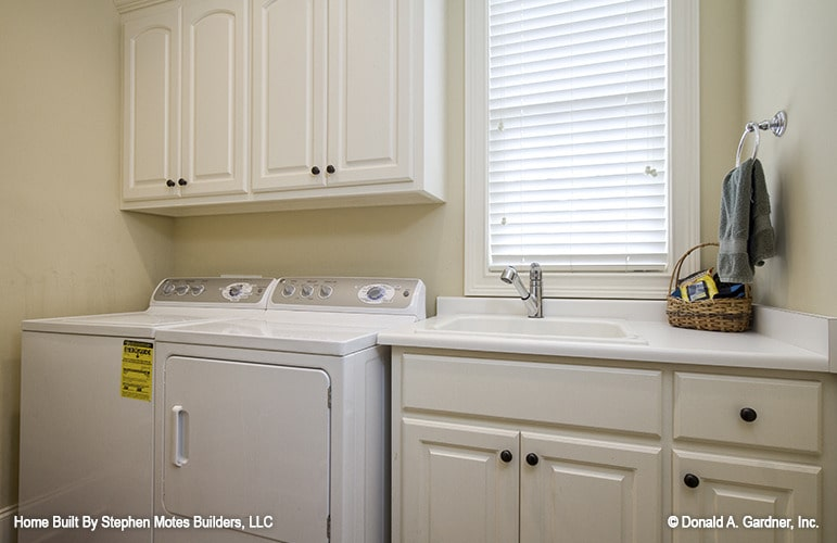 The utility room is equipped with a white washer and dryer, white cabinets, a porcelain sink, and a louvered window.