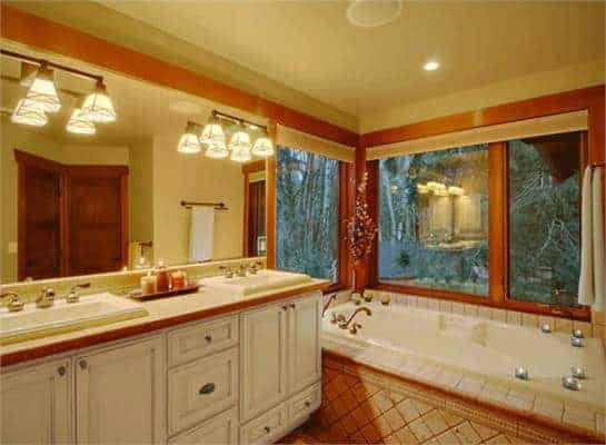 This is a close look at the bathroom with beige walls and ceiling accented with wooden beams that also make the white vanity cabinets and the white bathtub stand out.