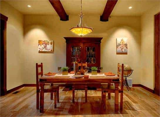 This is a mountain chalet dining room with a rectangular wooden dining table surrounded by wooden chairs and paired with a dark wooden dining cabinet that matches the exposed beams of the ceiling.