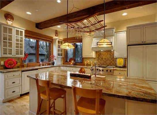 The large kitchen has a large kitchen island with a brown marble counter topped with a couple of pendant lights and a wooden hanging rack for wine glasses.