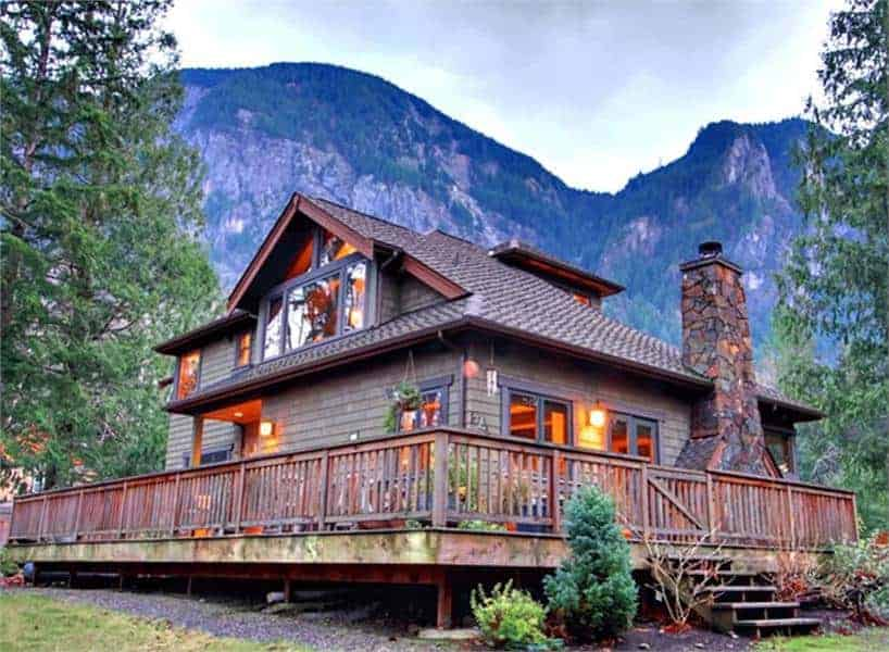This is a rear view of the moutain-style home that has a wrap-around balcony porch with wooden railings and walkway. These are then complemented by the surrounding landscape of trees and shrubs.