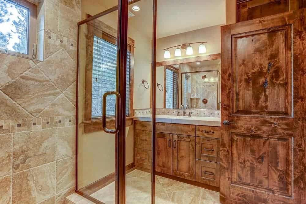 This mountain chalet-style bathroom has a large glass-covered shower area across from the vanity that has dark wooden cabinets and drawers that match the frames of the window and door.