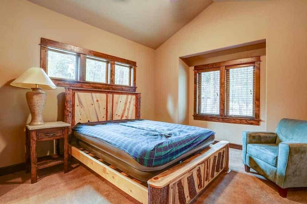 This is a simple mountain chalet-style bedroom with a rustic wooden platform bed that matches with the bedside table and the hardwood flooring. These are then complemented by the windows and the beige walls.