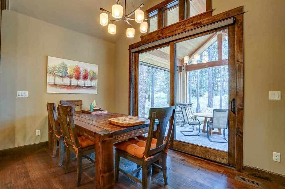 The small mountain chalet-style dining area has a rectangular wooden dining table surrounded by matching chairs and topped with a simple decorative chandelier. The wooden dining set also matches well with the hardwood flooring.