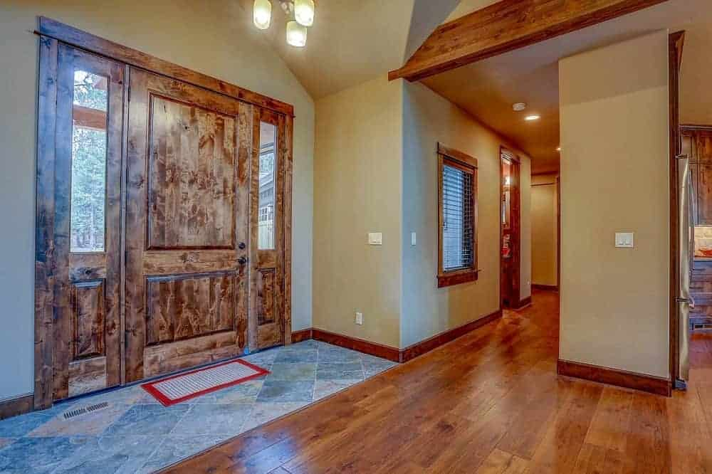 This is a simple mountain chalet-style foyer with a wooden main door that matches the hardwood flooring warmed by the simple lighting above and the beige walls. The foyer also has marble flooring before transitioning to hardwood.
