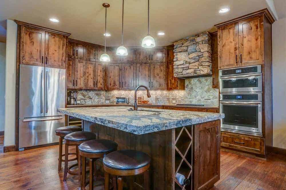 This is a full view of the mountain chalet-style kitchen with dark wooden cabinetry that blends with the hardwood flooring and kitchen island topped with a textured countertop and three pendant lights.