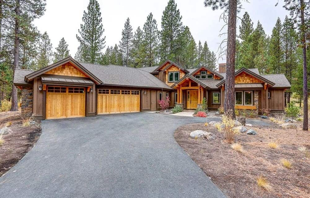 This is a view of the front of the mountain chalet-style home that has a wide asphalt driveway, wooden garage doors and landscaping of shrubs, trees and decorative rocks.