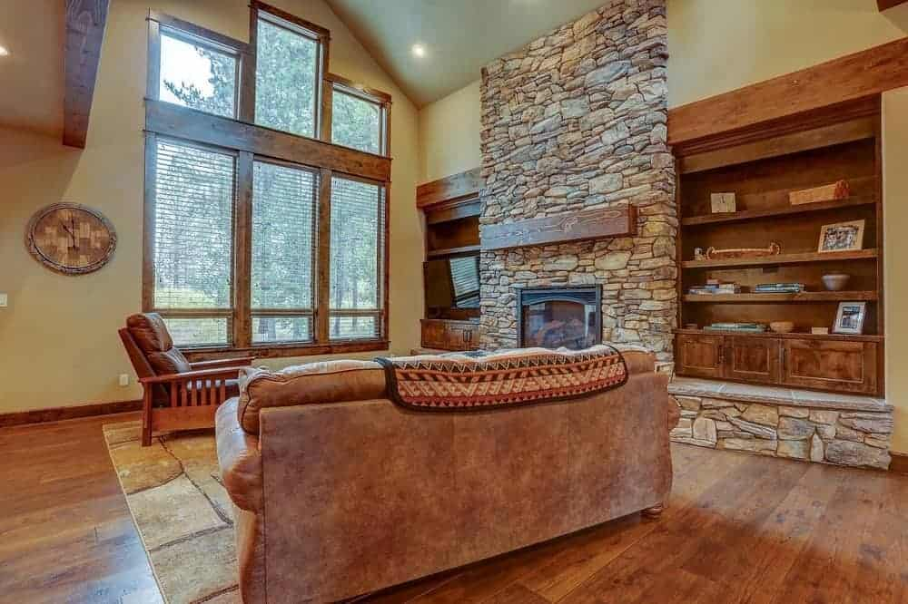 This is the large and airy mountain chalet-style living room that has a large glass wall on the far side to brighten the mosaic textured stone fireplace flanked by built-in shelves across from the brown leather sofa set.