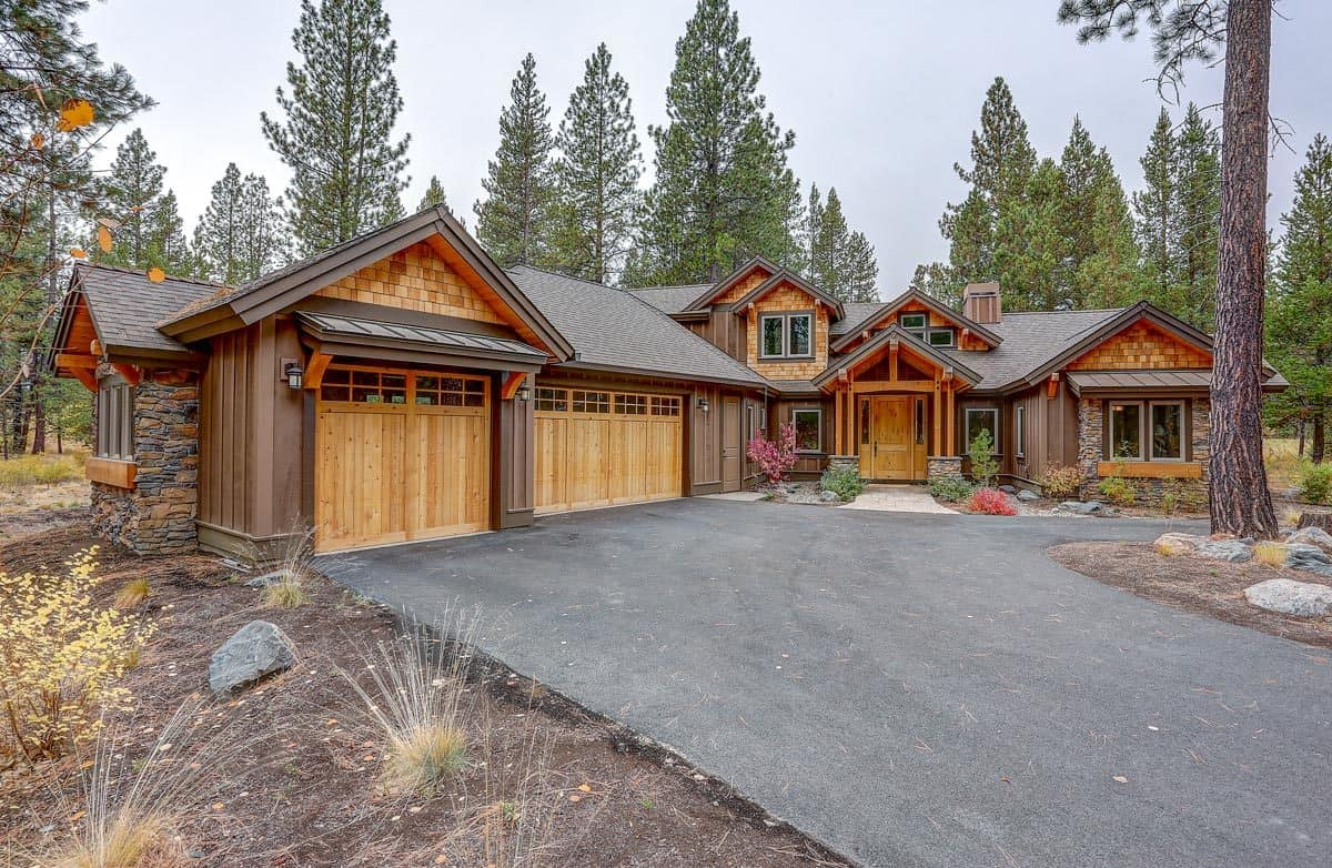 This is a close look at the front of the mountain chalet home with an asphalt driveway leading to wooden garage doors. This diverges to a concrete walkway leading to the main door that has wooden accents and beams complemented by the colorful shrubs.