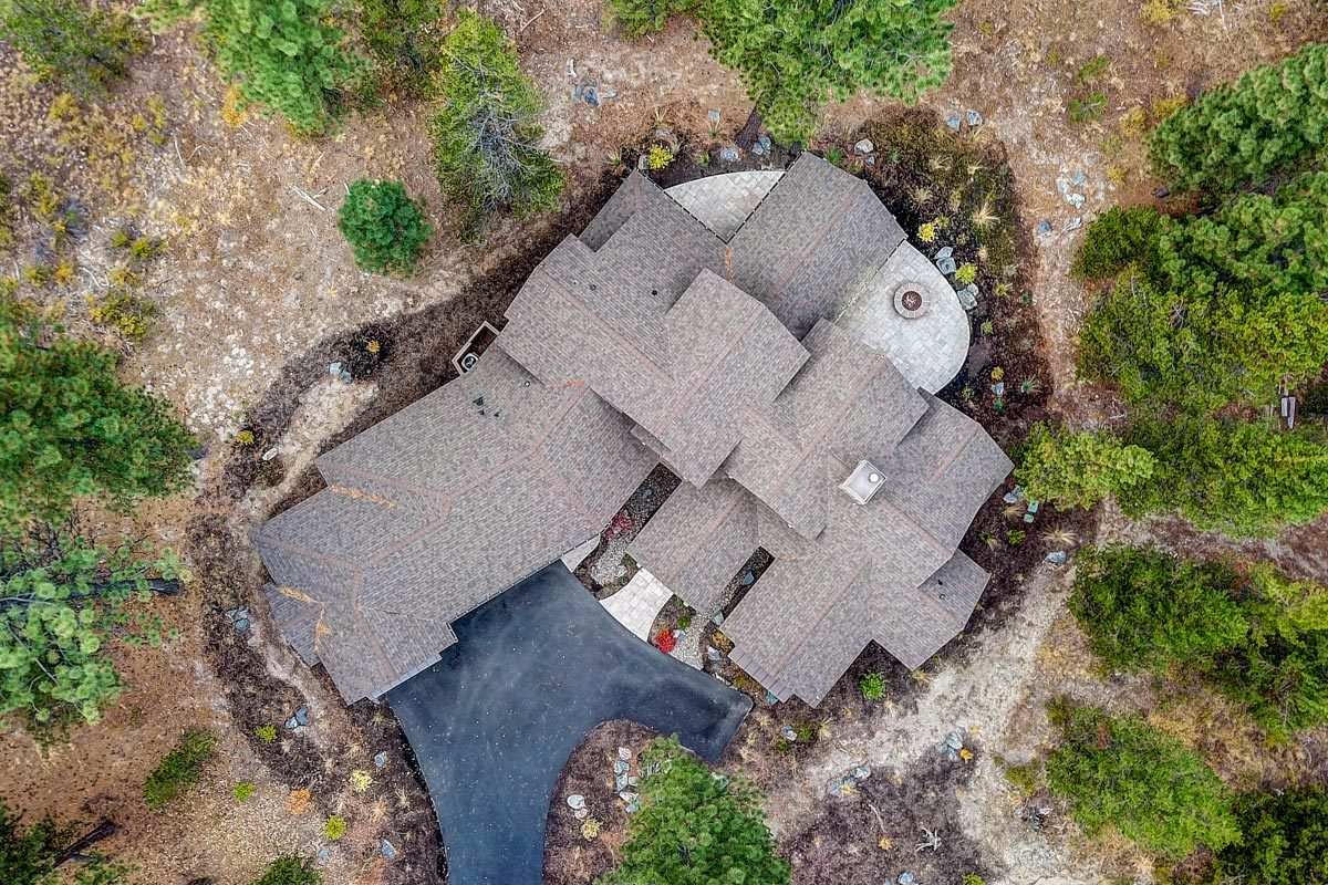 Bird's eye view of the mountain ranch showing its tiled roofs and concrete driveway.