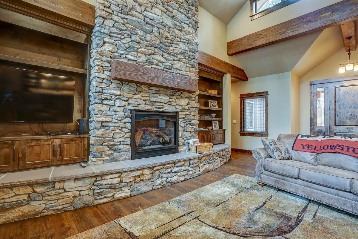 The living room includes clerestory windows and a stone fireplace flanked by wooden built-ins.