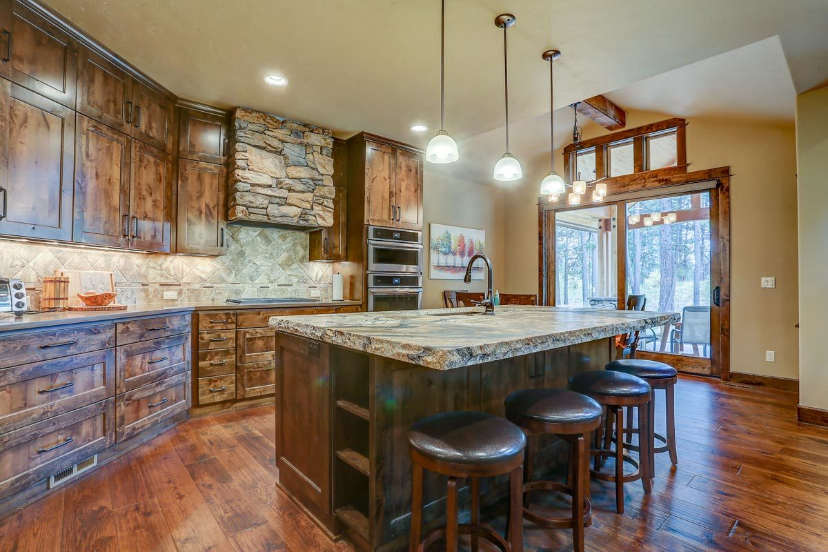 The kitchen offers natural wood cabinetry and a large multi-use island complemented with round bar stools.The kitchen offers natural wood cabinetry and a large multi-use island complemented with round bar stools.