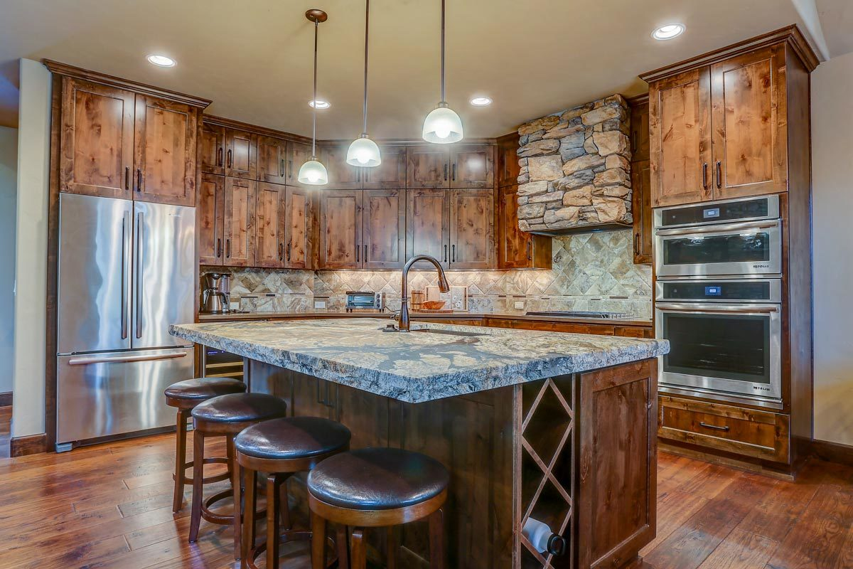 The kitchen island is fitted with an undermount sink and a wine rack arranged into a crisscross pattern.