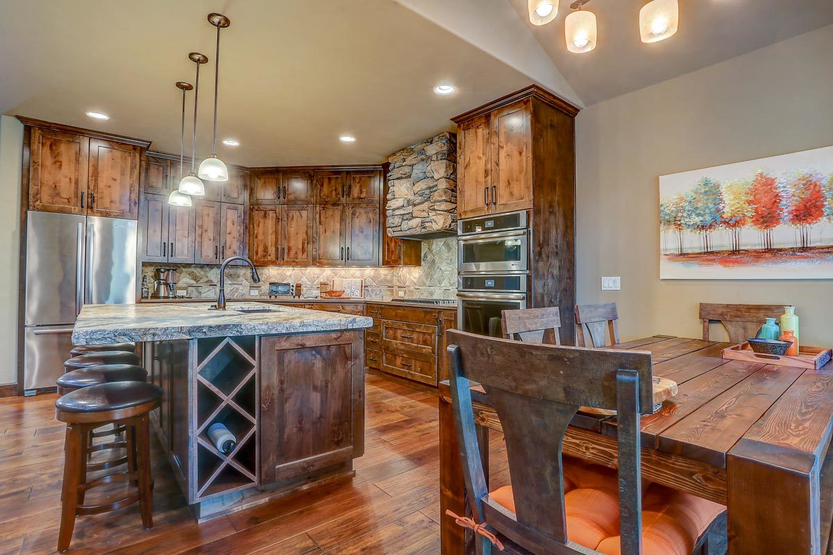 Glass pendants along with recessed ceiling lights enhance the cozy vibes in the eat-in kitchen.