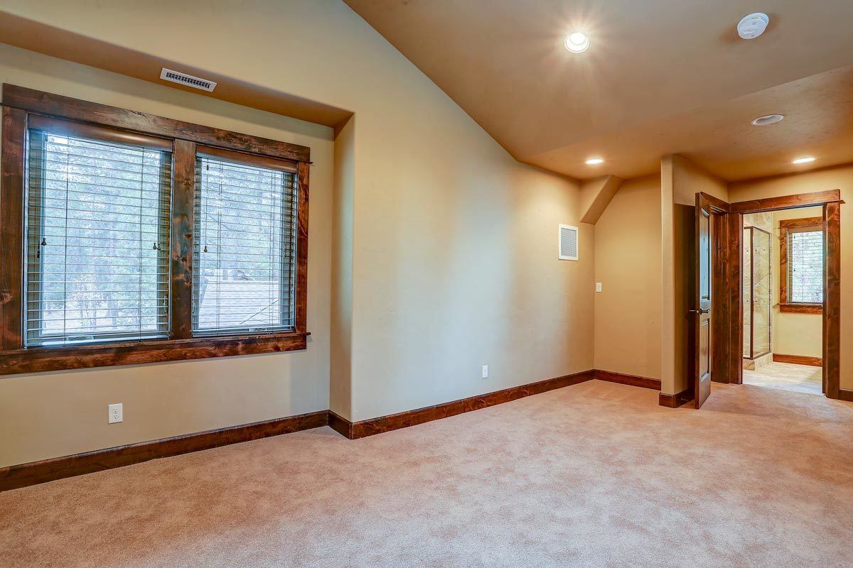Spare bedroom with carpet flooring, vaulted ceiling, and private bath.