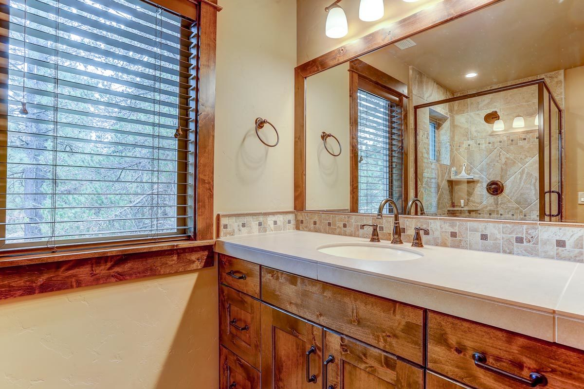 A closer look at the sink vanity with wooden cabinets, quartz countertop, and a large rectangular mirror.