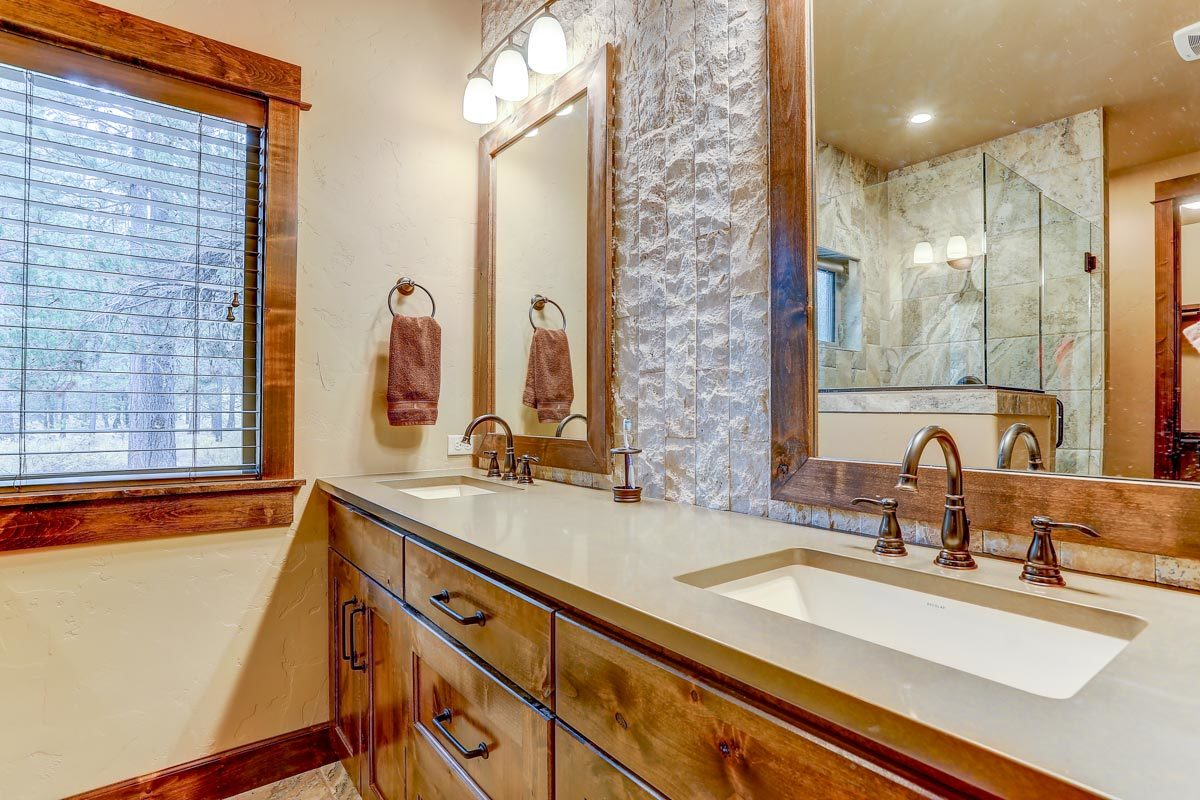 Another bathroom with wooden vanity equipped with double sinks and framed mirrors.