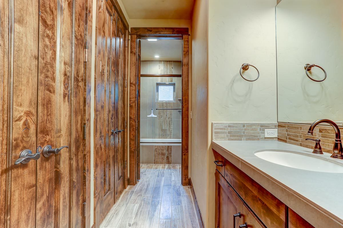 This bathroom offers a tub area, sink vanity, and walk-in closets concealed behind the two double doors.