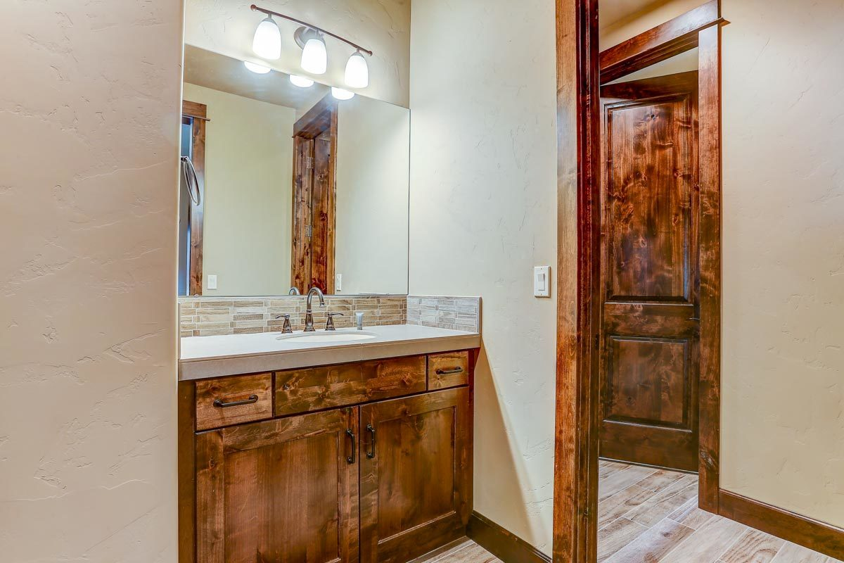 Frameless mirror and glass sconces complement the sink vanity.