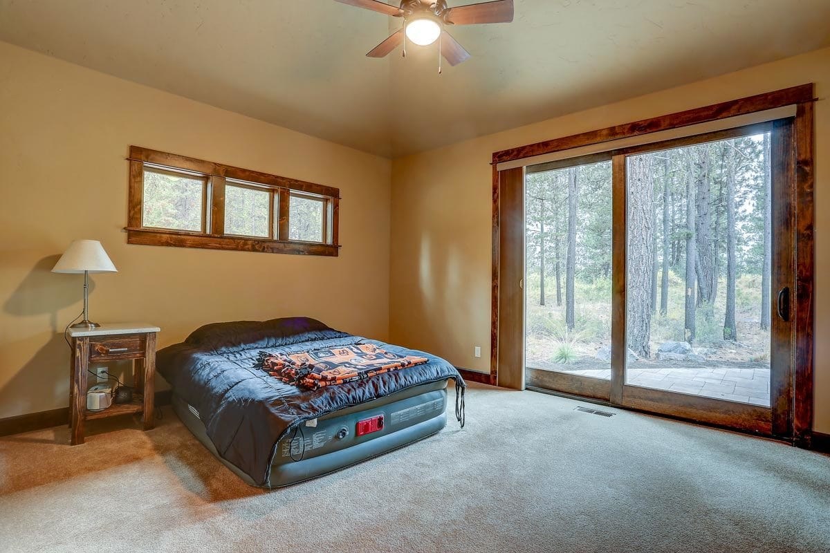 Primary bedroom with beige walls, carpet flooring, and sliding glass doors that open to the backyard.