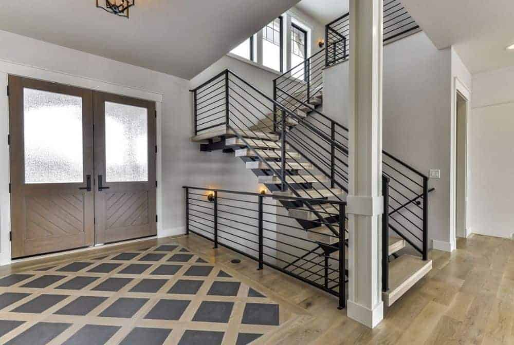 Foyer with a double entry door, a large patterned rug, and a staircase framed with wrought iron railings.