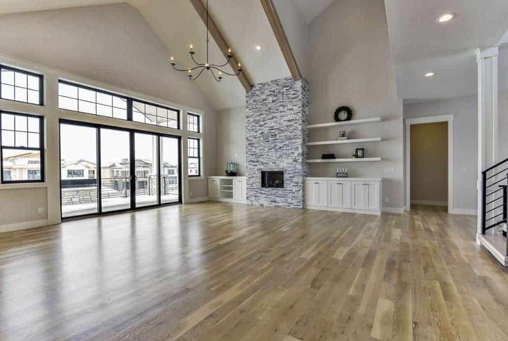 The living room has a brick fireplace, white built-ins, and a vaulted ceiling lined with exposed wood beams.