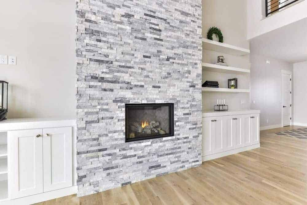 A closer look at the brick fireplace flanked by white base cabinets and floating shelves.
