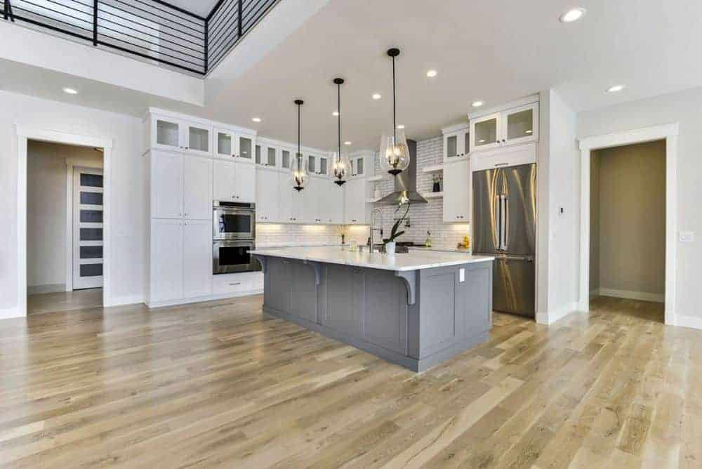 The kitchen is equipped with stainless steel appliances, marble countertops, white cabinetry, and a large center island.