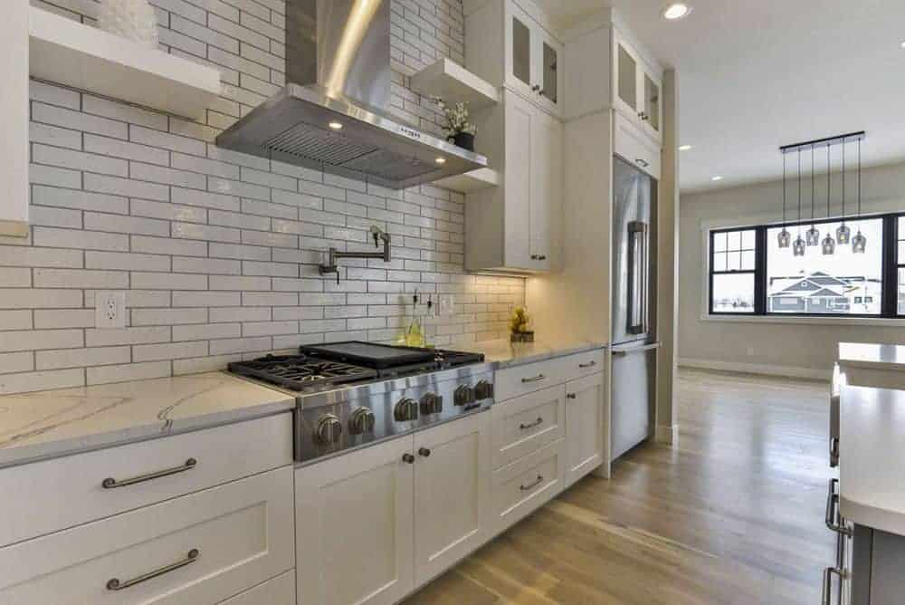 The kitchen includes a subway tile backsplash and a built-in cooktop paired with a sleek vent hood.