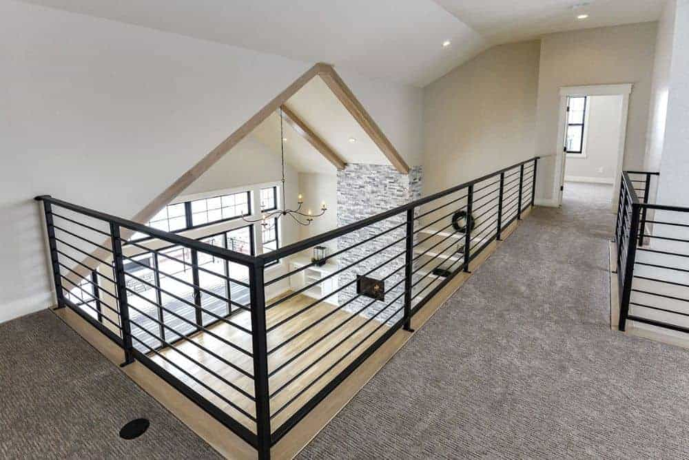 Balcony loft with carpet flooring bordered by wrought iron railings.