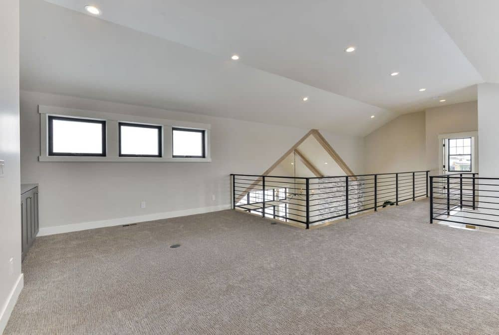 The balcony loft has small windows, a bar, and a vaulted ceiling fitted with recessed lights.