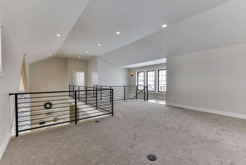 The bridge-style hallway leads to the bedroom suite.