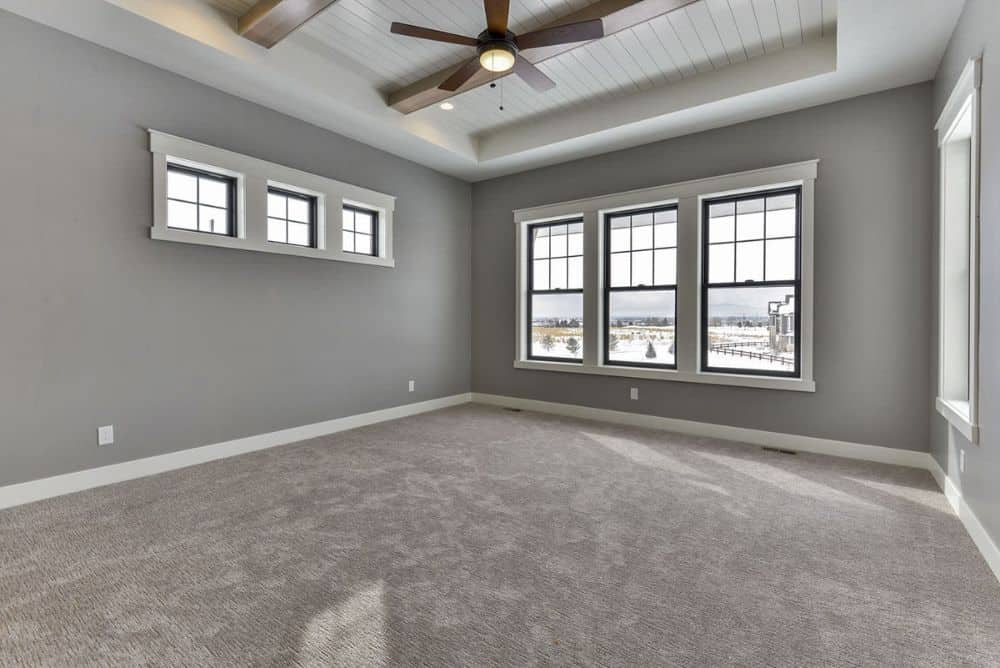 Primary bedroom with gray walls, carpet flooring, a beamed tray ceiling, and lots of framed windows.