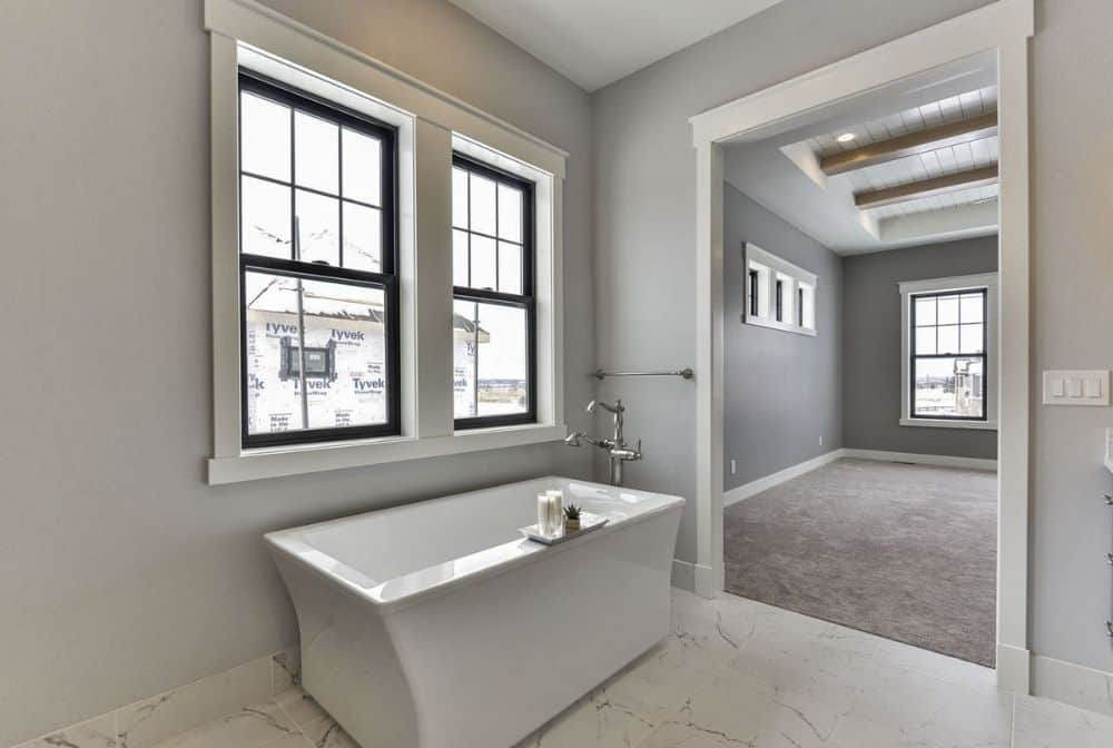 The freestanding tub over marble tile flooring is situated underneath the framed windows.