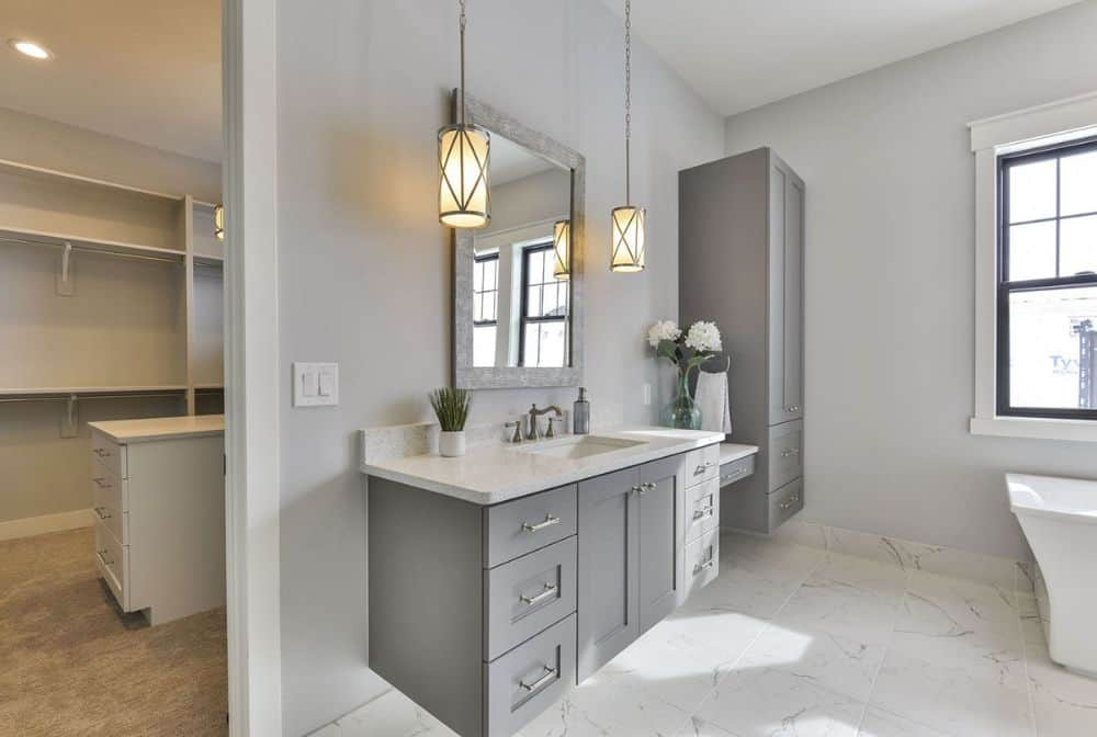 The primary bathroom features a sink vanity attached with a makeup counter and a tall floating cabinet.
