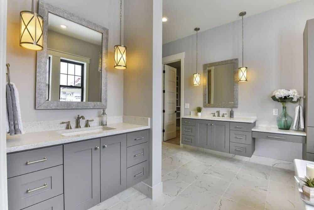 There's another sink vanity paired with a framed mirror and warm glass pendants.