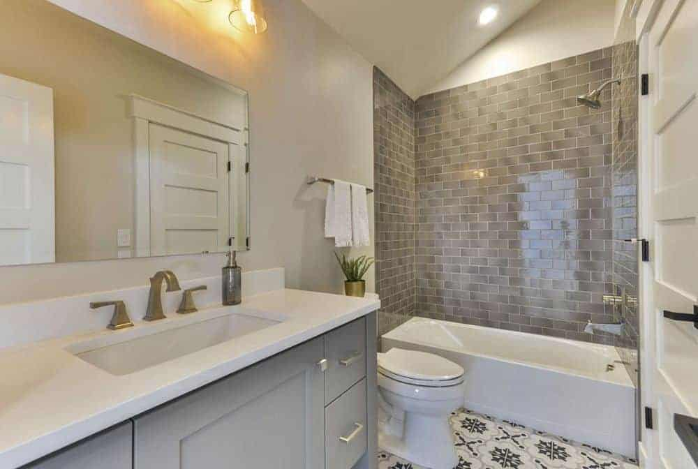 This bathroom offers a sink vanity, a toilet, and a tub and shower combo.