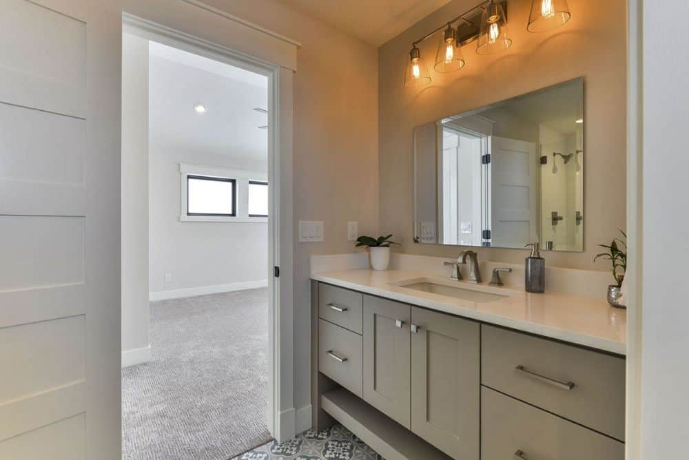 The sink vanity is complemented with a frameless mirror and warm glass sconces.
