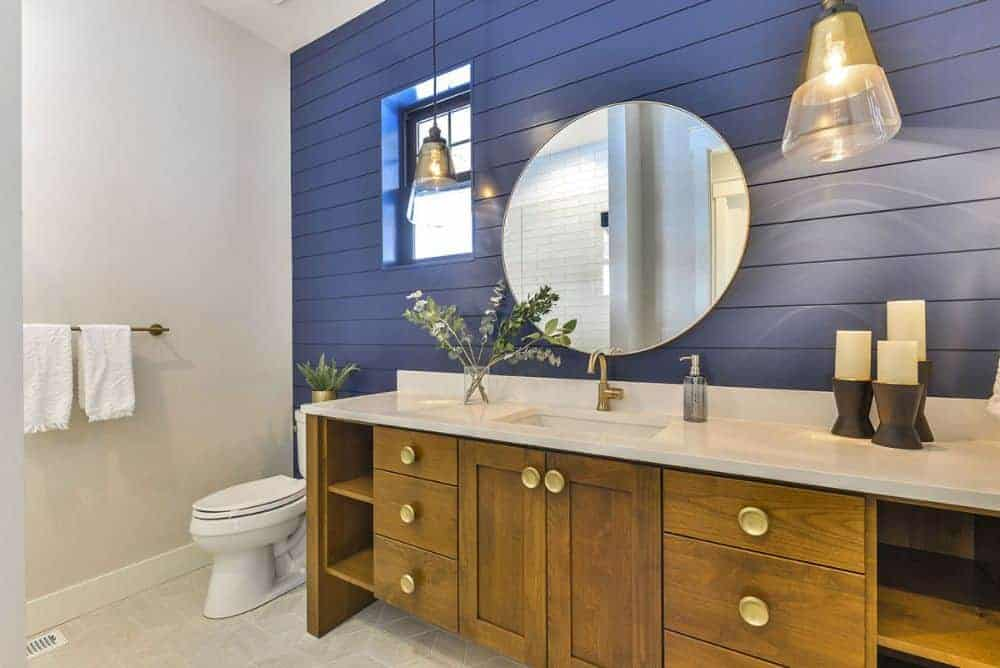 Powder room with a toilet and a large sink vanity placed against the blue shiplap wall.