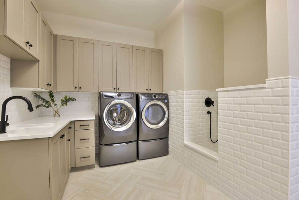 Laundry room with taupe cabinets, front-load appliances, a utility sink, and a wash area.