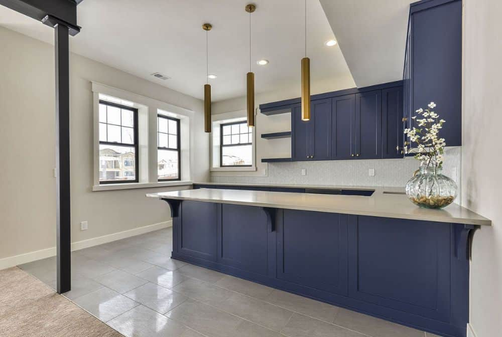 Basement with a large wet bar composed of blue cabinets, quartz countertops, and cylindrical pendants.
