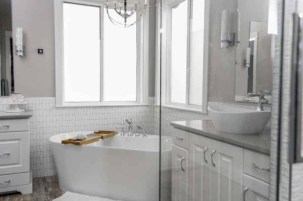 This is a close look at the bright bathroom that has a freestanding bathtub at the far corner under two windows next to the glass-enclosed shower area and white vanity that blends well with the backsplash tiles.